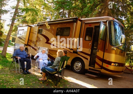 People sitting near recreational vehicle - Stock Photo