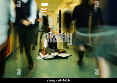Girl in crowded school hallway with books on the floor - Stock Photo