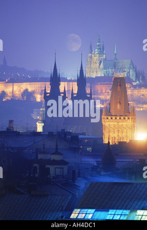 The city of 100 spires and Prague Castle or Hradčany Castle with St Vitus Cathedral under full moon at night - Stock Photo