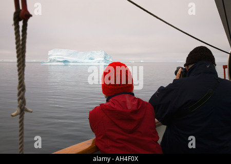 Couple on cruise ship taking photo of big iceberg passing by on calm seas in Disko Bay off the west coast of Greenland - Stock Photo