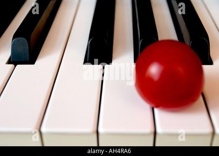 Piano keyboard close up with alone solo tomato - Stock Photo