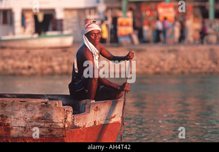 Fisherman in boat at sunset Stone Town waterfront Zanzibar Tanzania East Africa - Stock Photo