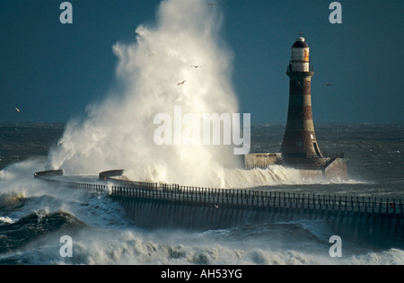 Huge wave breaks over the lighthouse on Roker Pier, Sunderland, England, UK, during a winter storm - Stock Photo