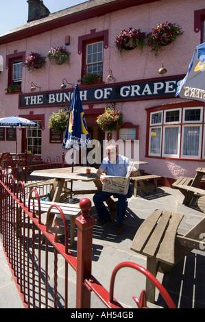 Man reading paper outside The Bunch of Grapes pub, Newcastle emlyn Carmarthenshire Wales Cymru UK - Stock Photo