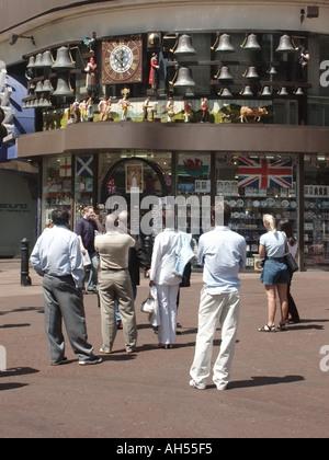 Street scene Swiss Centre tourist information shop & people watch revolving clock display of cows milkmaids & Glockenspiel Leicester Square London UK
