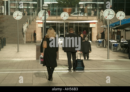 Canary Wharf London Docklands office areas people in pedestrian only areas walking passed repetitive clock faces - Stock Photo