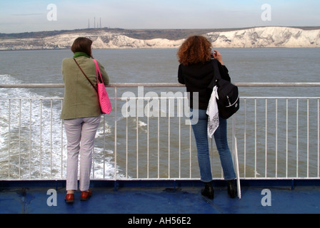 English Channel off Kent coast 2 two passengers on ferry English white chalk cliffs distant - Stock Photo