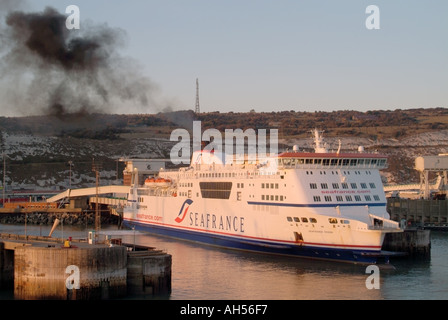 Dover harbour Seafrance Rodin moored at loading berths in ferry terminal discharging black smoke white cliffs beyond - Stock Photo