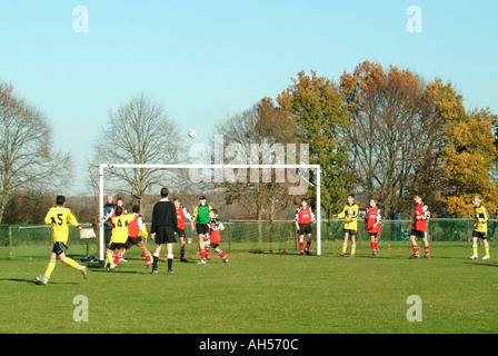 Back view of referee controlling youth football match (ball in the air) - Stock Photo