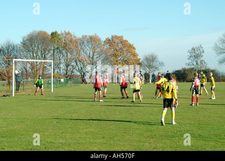 Children wearing team kit playing football match with spectators & parents beyond Brentwood Essex England UK - Stock Photo