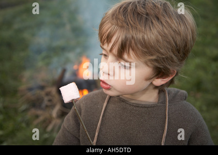 boy with marshmallow on stick - Stock Photo