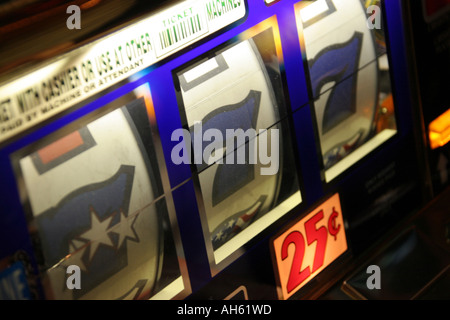 Three Lucky Sevens on a one armed bandit in a casino in Las Vegas - Stock Photo
