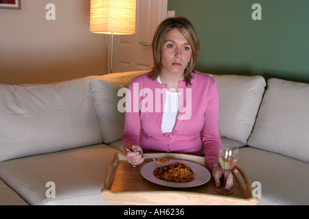 Young woman on sofa watching TV and eating dinner from a tray unhappy expression - Stock Photo