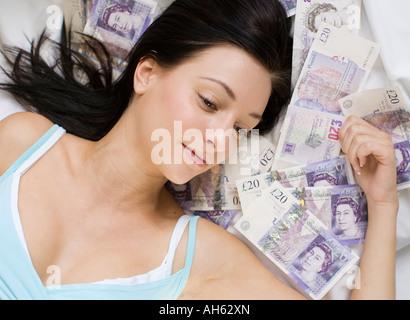 Girl lying on twenty pounds notes - Stock Photo