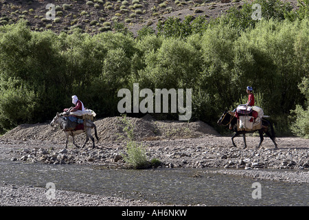 Europeans tourist doing mule trekking by a river in Morocco