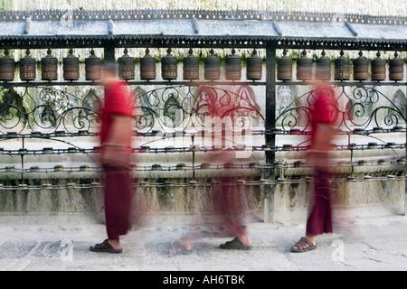 Long Exposure of Buddhist monks walking around Swayambhu stupa, Kathmandu Nepal - Stock Photo