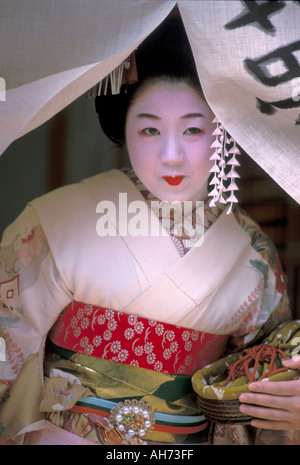 A tourist dressed as a maiko, or geisha in training, posing at a doorway curtain on her way outside - Stock Photo