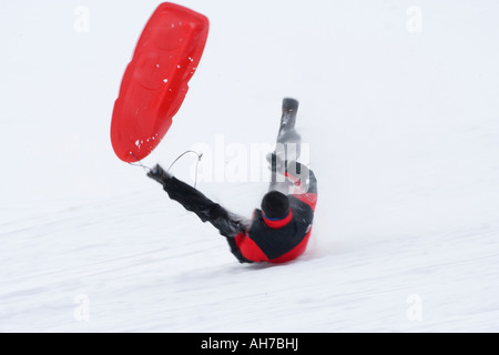 Mid adult man sliding downhill - Stock Photo