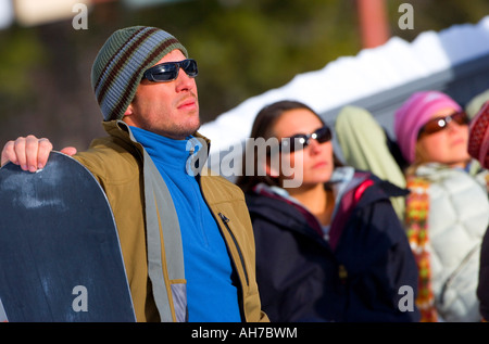 Mid adult man holding a snowboard with two women behind him - Stock Photo