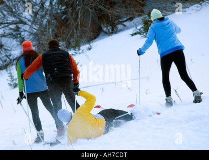Rear view of three people skiing and one man falling - Stock Photo