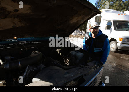 Mid adult man standing beside a sport utility vehicle - Stock Photo
