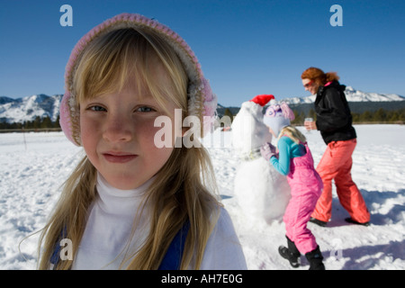 Portrait of a girl with her mother and sister in the background - Stock Photo