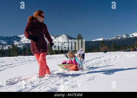 Mature woman pulling her daughters on a sled - Stock Photo