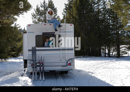 Mature woman sitting on top of a recreational vehicle with her two daughters inside it - Stock Photo