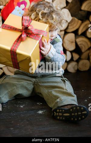 Boy holding a Christmas present - Stock Photo