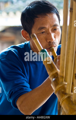 Dong Man Playing Complex Traditional Wooden Flute Zhaoxing China - Stock Photo