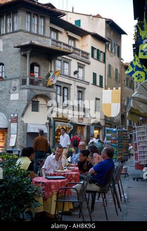 Young people sit at restaurant tables in Piazza della Repubblica Cortona Tuscany Italy - Stock Photo