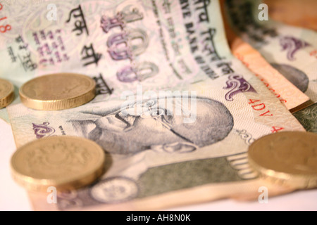 A collection of Indian notes and coins stacked together - Stock Photo