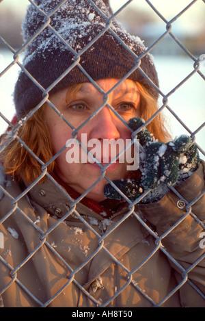 Homeless woman age 50 peering through chain link fence.  St Paul Minnesota USA - Stock Photo