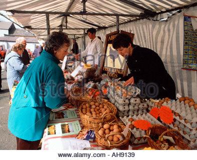Woman buying free range eggs from organic farm stall Macclesfield farmers market Cheshire UK - Stock Photo