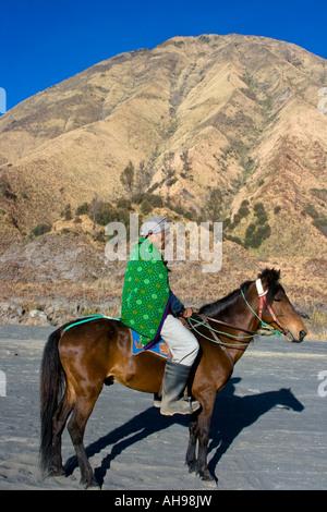 Tengger Man on Horseback in front of Mt Batok Waiting to take Tourists to the rim of Gunung Bromo or Mount Bromo - Stock Photo