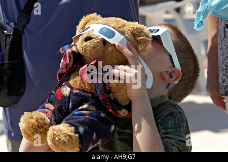 Young boy with teddy bear and solar viewer safety glasses watching the initial stages of the Total Eclipse of the - Stock Photo
