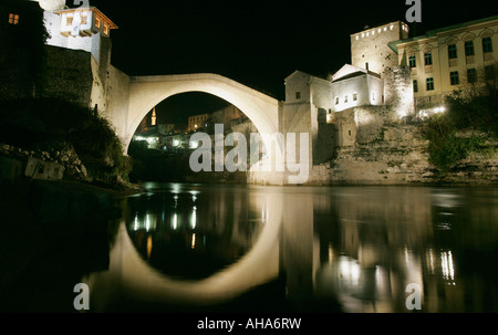 Stari Most the Old Bridge over the Neretva River is illuminated at night in Mostar in Bosnia Herzegovina - Stock Photo
