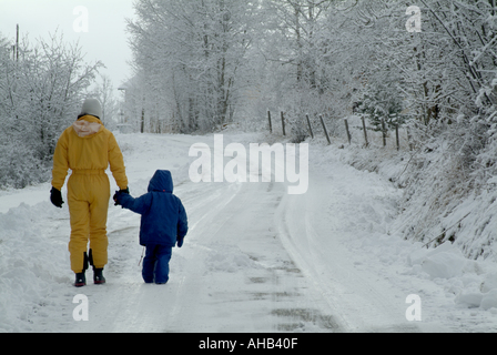 Mother and her three year old daughter walking along a snowy road, Selonnet, French Alps, France. - Stock Photo