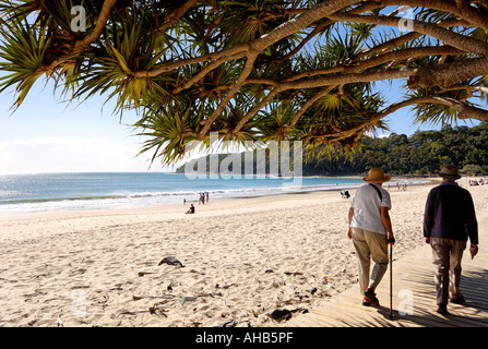 An old couple walking along a pandanus palm lined boardwalk beside a beach with the sand and surf in the background. - Stock Photo