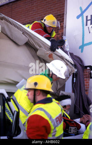 Firefighters cut free a victim of a road traffic accident The face of the victim has been obscured - Stock Photo