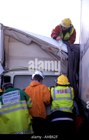 Firefighters cut free a victim of a road traffic accident Victim is not visible - Stock Photo