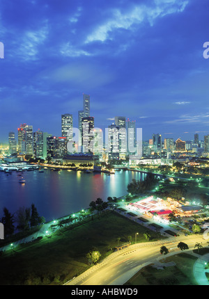 Central business district of Singapore over Marina Park at night - Stock Photo