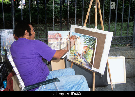 Artist painting on pavement, Jackson Square, Decatur Street, French Quarter, New Orleans, Louisiana, USA - Stock Photo