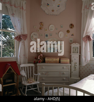 Child s white rocking chair and stencilled white chest of drawers in pink bedroom with white curtains and pink tiebacks - Stock Photo