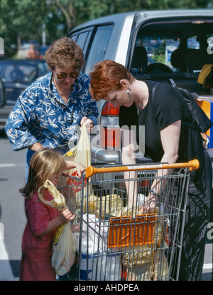 MOTHER DAUGHTER AND GRANDMOTHER LOADING CAR FROM TROLLEY IN SUPERMARKET CAR PARK UK - Stock Photo