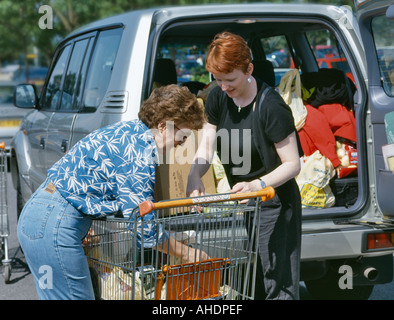 MOTHER AND DAUGHTER LOADING CAR 4X4 FROM TROLLEY IN SUPERMARKET CAR PARK UK - Stock Photo