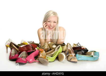 Woman smiling with pile of shoes in front of her - Stock Photo