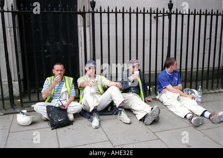 Group of workmen taking lunch break from work on pavement in central London. - Stock Photo