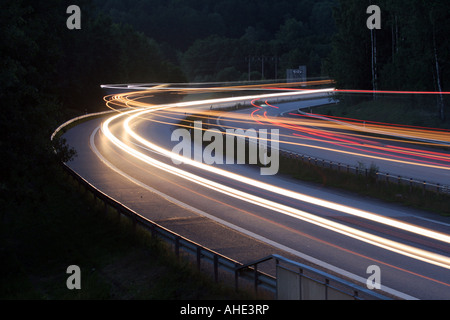 Light trails from cars and trucks on a motorway at night - Stock Photo