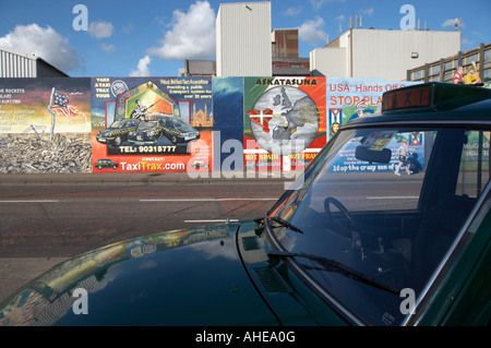 Falls road black taxi parked across the road from the International wall murals in the republican falls road area - Stock Photo